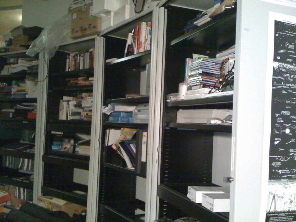 Some untidy shelves, full of geek stuff